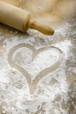 homemade style: Hand drawn heart in sprinkled flour with a wooden rolling pin showing a love and enjoyment of cooking and baking