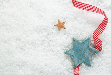 seasonal greetings: Christmas star background with a decorative red and white checked ribbon on a backdrop of winter snow with copysapce for your seasonal greetings