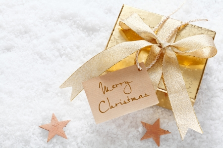 christmass: Gold gift with a decorative ribbon and Merry Christmas tag nestling on fresh snow with stars and copyspace