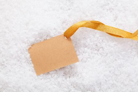 Empty blank paper label and gold ribbon lying in winter snow ready for your Christmas greeting photo