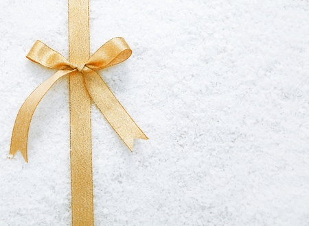 christmass: Decorative simple gold ribbon and bow on a background of winter snow with copyspace for your Christmas or festive greeting