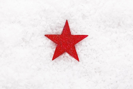 Colourful red Christmas star decoration on winter snow centred in the image with copyspace all around for your seasonal message photo