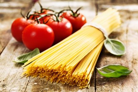 İtalyan mutfağı: Eski ve vintage ahşap masa üzerinde otlar ile spagetti ve domates
