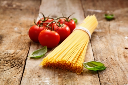 truss: Bucnch of raw spaghetti with a truss of tomatoes in a rustic scene