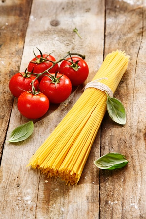 Spaghetti and tomatoes with copyspace on a wood background photo