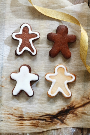 4 Gingerbread men on a grunge baking paper for christmas food and cookie concept photo