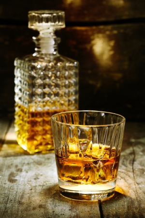 Glass and bottle of hard liquor like scothc, bourbon, whiskey or brandy on wooden background with copyspace photo