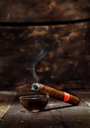 hombre fumando puro: Burning cigarro cubano lujo hecho a mano descansando sobre un cenicero en una encimera de madera vieja en una discoteca o bar con copyspace