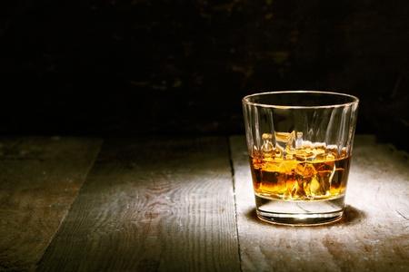 whiskey: Scotch op houten achtergrond met copyspace. Een oude en vintage aanrecht met hoogtepunt en een glas sterke drank