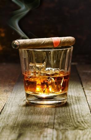 Brennende kubanische Zigarre ruht auf einem Glas Schnaps in einer Bar, die luxuriösen Annehmlichkeiten eines wohlhabenden Macho Standard-Bild