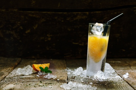 shooter drink: Alcohol Orange Shot Drink with copyspace, on brown wooden board. Stock Photo
