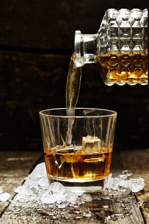 Pouring Whiskey or Scotch from carafe into a glass with ice cubes photo