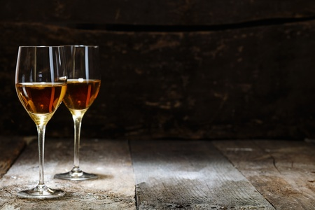 spirituous beverages: Two glasses of sherry on brown wooden background with copyspace