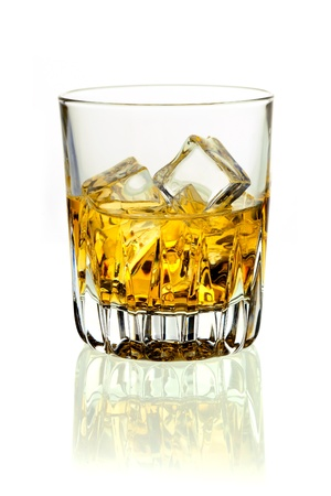 aperitif: Closeup of a glass of golden whiskey on ice on a white background with reflection