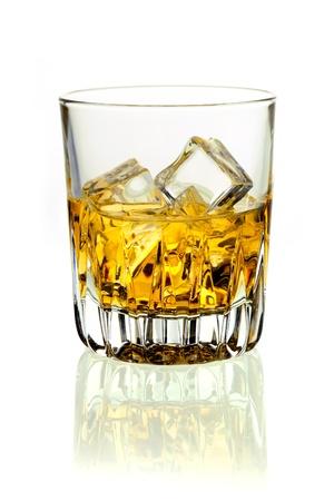whisky: Gros plan d'un verre de whisky d'or sur glace sur un fond blanc avec la r�flexion