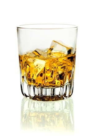 shooter drink: Closeup of a tumbler of glowing golden brandy and ice on a white background with relection Stock Photo