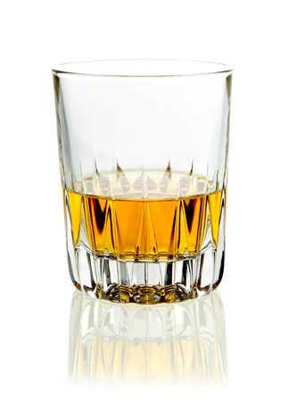 Tumbler of golden whisky or brandy served neat on a white studio background with reflection photo
