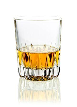 whiskey: Tumbler van gouden whisky of cognac geserveerd nette op een witte studio achtergrond met reflectie