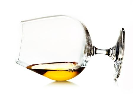 distilled: Glowing cognac o brandy d'oro in un bicchiere bicchierino di liquore sdraiato su un fianco su uno sfondo bianco
