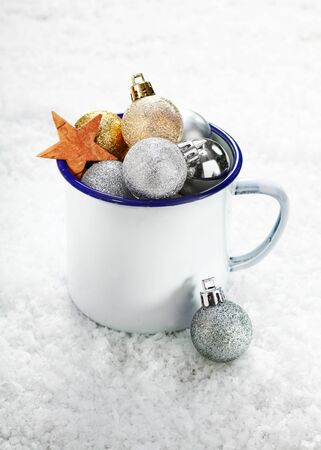 Christmas decorations in an enamelled tin mug on snow which is full to overflowing with baubles and stars photo