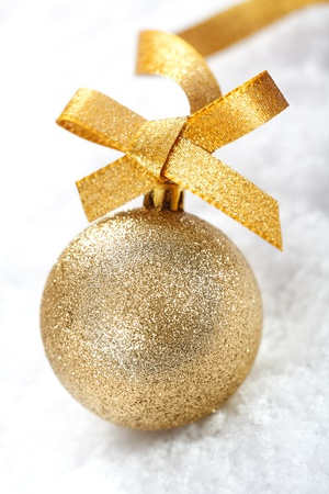 Closeup of a shiny gold glitter Christmas bauble with a decorative golden ribbon and bow on snow photo