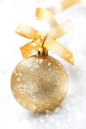 christmass: Glittering gold Christmas ball with an ornamental gold bow in winter snow with falling snowflakes