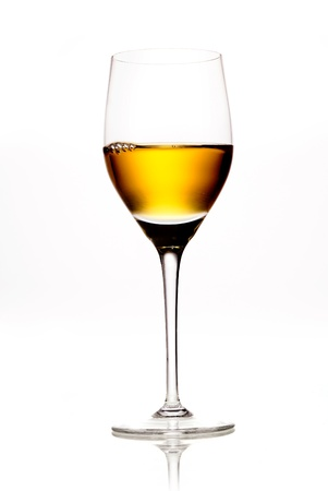 aperitif: Elegant wineglass full of amber coloured wine or sherry on a white background with reflecton Stock Photo