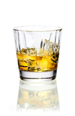 shooter drink: Glass of golden whiskey or brandy served on ice on a reflective white surface