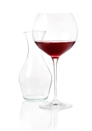 Glass of red wine with an empty glass carafeon a reflective white surface Stock Photo - 15394036