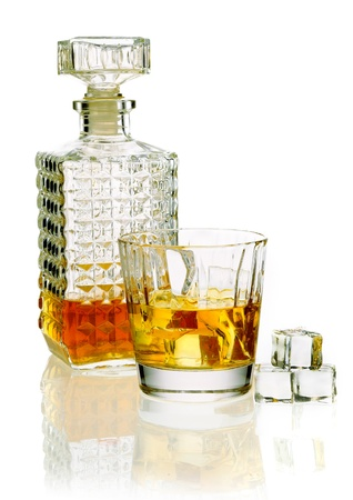 Whiskey or brandy decanter with a glass of whiskey on a reflective white surface Stock Photo - 15394096