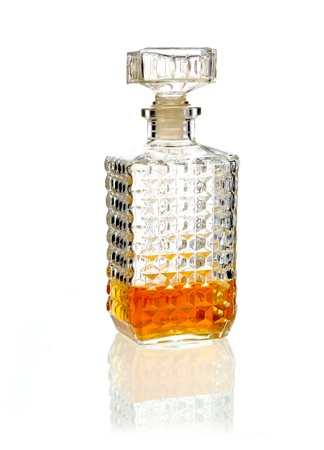 Stoppered whiskey or brandy decanter one third full of alcohol on a reflective white surface Stock Photo - 15394094