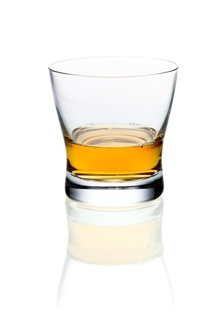 whisky glass: Glass of golden brandy or whisky on a white background with reflection