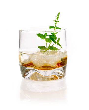 longdrink: Alcoholic Drink with mint and ice cubes . Hard Liquor in a glass with ice and some herbs isolated on white background