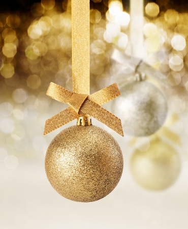 christmass: Hanging golden glitter textured Christmas ornament against a background of twinkling party lights Stock Photo