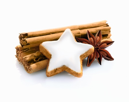 christmass: Christmas spice still life with cinnamon stiicks and star anise and a decorative star shaped iced biscuit on a white background