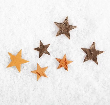 christmass: Seasonal or Christmas background of scattered rustic stars on fresh white winter snow with copyspace