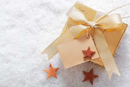 Decorative gold Christmas gift in winter snow with a blank label for your seasonal greeting and a scattering of small stars