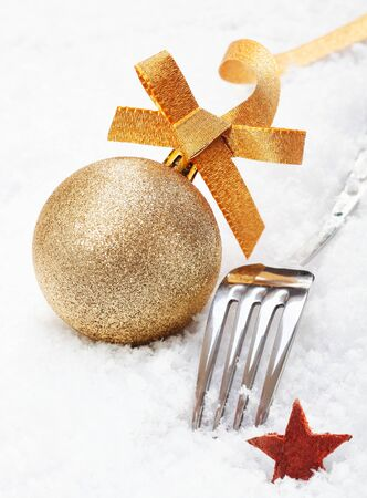 Shiny silver Christmas fork and ornamental gold glitter bauble with a star in soft white winter snow photo
