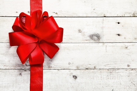 holiday celebration: Decorative red ribbon and bow on a background of white painted rustic boards with copyspace Stock Photo