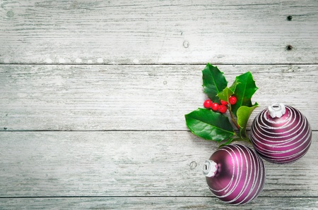 woodgrain: Christmas holly and pretty purple baubles with a spiral pattern on rustic wooden white painted boards with woodgrain texture and plenty of copyspace