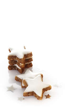 estrella de la vida: Tasty crujiente galleta de Navidad golosinas con forma de estrellas en una formación de hielo cubiertos de nieve blanca sobre un fondo blanco con copyspace Foto de archivo