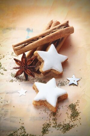 vignetting: Christmas cinnamon and star anise spice with decorative whited iced star biscuits on vintage paper with vignetting