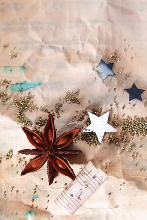 christmas music: Grungy Christmas background with crumpled old paper scattered with stars , a star anise spice and part of a music score with copyspace