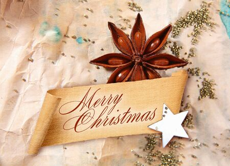 Merry Christmas Greeting on curled banner with star anise spice and a star arranged on crumpled aged paper photo