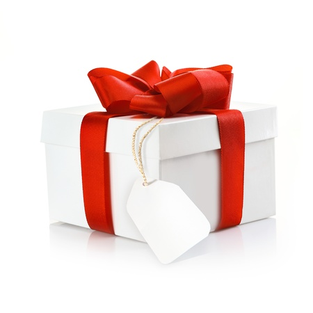 gift background: Christmas surprise gift with blank tag and a decorative red ribbon and bow on a white studio background