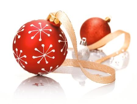 decoraciones de navidad: Elegante rojo de la Navidad de fondo con una chuchería con dibujos de copos de nieve y una cinta decorativa sobre una superficie reflectante blanco estudio Foto de archivo