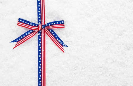 patriot: Decorative patriotic American ribbon and bow with the stars and stripes on winter snow for your Christmas greeting