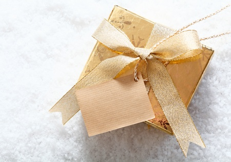 Gold gift box standing in snow with a pretty bow and a blank tag for your festive Christmas greeting photo
