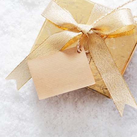 Gold Christmas giftbox with blank paper label and decorative ribbon and bow standing on a bed of fresh winter snow photo