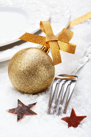 Christmas winter place setting on snow with silver cutlery decorated with a golden bauble and stars photo